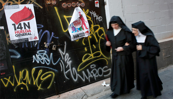 Two nuns walks past banners that read '14N