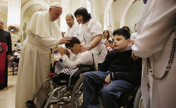 pope francis blesses a disabled person during his visit at the serafico institute in assisi