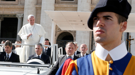 A Swiss Guard watches as Pope Francis leaves his general audience in St. Peter's Square at the Vatican Oct. 16. (CNS photo/Paul Haring)