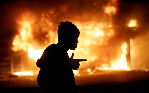 A man walks past a burning building during rioting in Ferguson