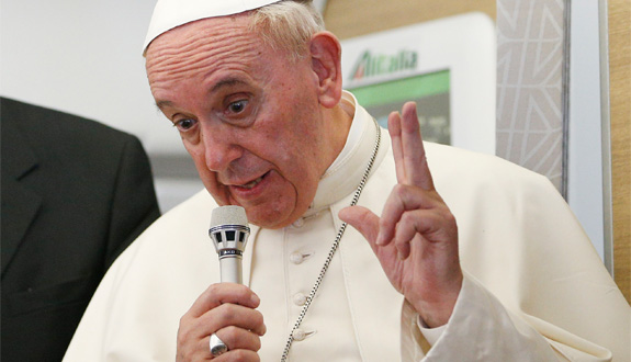 Pope Francis gestures as he answers questions from journalists aboard his flight from Bangui