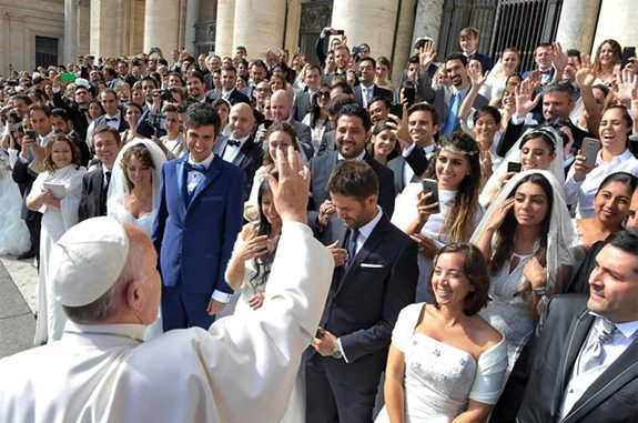 Pope Francis greets newly married couples during his general audience in St. Peter's Square at the Vatican in this Sept. 30