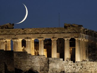 The moon is seen behind the ancient temple of the Parthenon in Athens