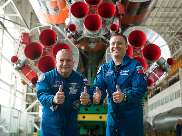 """jsc2017e043850 (April 14, 2017) --- In the Integration Facility at the Baikonur Cosmodrome in Kazakhstan, Expedition 51 crewmembers Fyodor Yurchikhin of the Russian Federal Space Agency (Roscosmos, left) and Jack Fischer of NASA (right) provide a """"thumbs up"""" as they pose for pictures April 14 in front of their Soyuz booster rocket. Fischer and Yurchikhin will launch April 20 on the Soyuz MS-04 spacecraft for a four and a half month mission on the International Space Station. Credit: NASA/Gagarin Cosmonaut Training Center/Andrey Shelepin"""