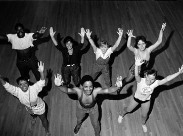 black and white image of 7 student dance performers reaching up to the camera. one woman wears parachute pants, in the 80's style.