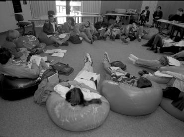 about 12 students in discussion sitting on bean bag chairs that circle a room