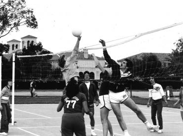students from the 1970s playing volleyball. Men wearing short shorts in the 70's style.