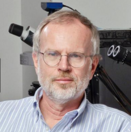 Roeland Nusse face and shoulders, with light grey beard, light blue shirt, sitting with background of microscope