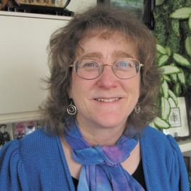 Eleanor Levin wearing blue shirt and blue/purple scarf, blonde hair, wire framed glasses