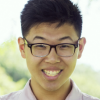 Photo of Jason Li as a White House E3! Ambassador. Front full face smiling image with black rimmed glasses, dusty pink open collared shirt with muted sunlit greenery in the background