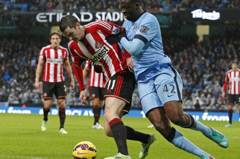 """Manchester City's Ivorian midfielder Yaya Toure (R) vies with Sunderland's English midfielder Adam Johnson during the English Premier League football match between Manchester City and Sunderland at the Etihad Stadium in Manchester, north west England, on January 1, 2015. AFP PHOTO / LINDSEY PARNABY  RESTRICTED TO EDITORIAL USE. No use with unauthorized audio, video, data, fixture lists, club/league logos or """"live"""" services. Online in-match use limited to 45 images, no video emulation. No use in betting, games or single club/league/player publications. / AFP / LINDSEY PARNABY"""