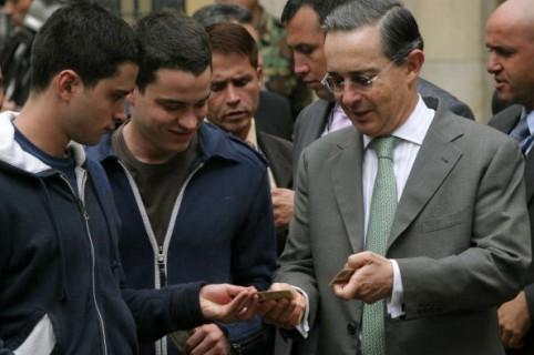 COLOMBIA - MAY 28:  Colombian President Alvaro Uribe looks at the identification cards of his sons, Jeronimo, left, and Tomas, center as he lines up to vote during presidential elections in Bogota, Sunday, May 28, 2006. Uribe is likely to be re-elected today as voters back his successes in combating guerrilla violence and overseeing the country's fastest economic expansion in a decade.  (Photo by Marcelo Salinas/Bloomberg via Getty Images)