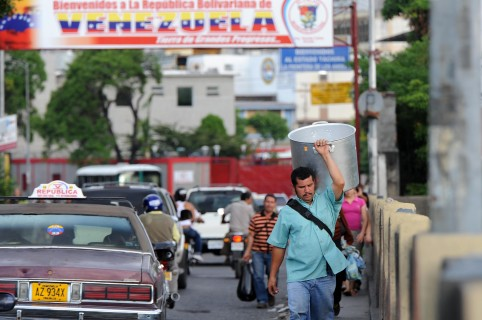 A man carrying a big pan crosses the Simon Bolivar bridge that connects Colombia with Venezuela, in Cucuta, Colombia, on November 21, 2009. AFP PHOTO/Guillermo LEGARIA (Photo credit should read GUILLERMO LEGARIA/AFP/Getty Images)