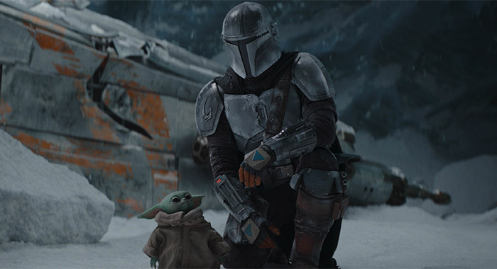 Pedro Pascal as The Mandalorian with The Child (aka Baby Yoda) in The Mandalorian season 2