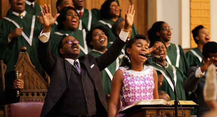 Choir and Rev C.L. Franklin, played by Courtney B. Vance, behind Little Re, played by Shaian Jordan, as she performs her first solo in her father's church. (Credit: National Geographic/Richard DuCree)