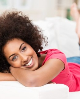 Beautiful laid-back African American woman relaxing barefoot on her stomach on the sofa at home smiling at the camera