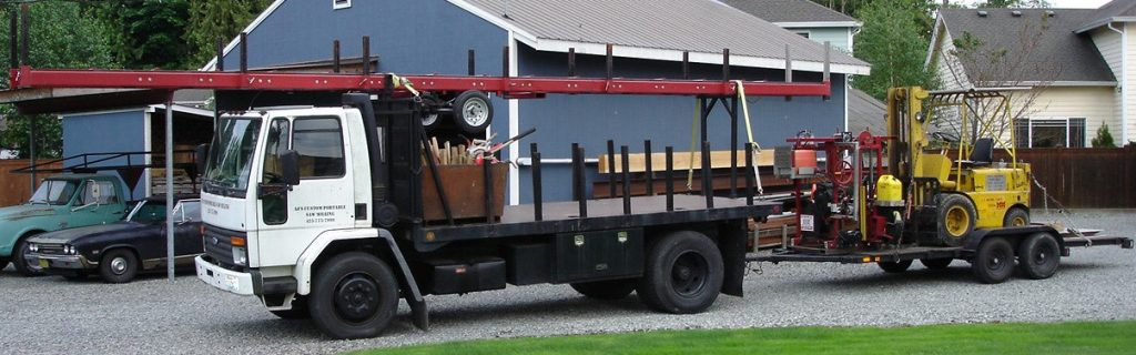 Flat-bed truck with mobile milling equipment and a small forklift