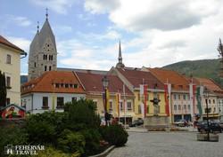 Friesach főtere, háttérben a román stílusú plébániatemplom