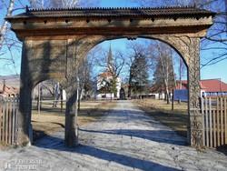 székelykapu Farkaslakán, a háttérben Tamási Áron síremléke