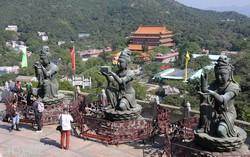 buddhista istenségek szobrai Lantau szigetén, háttérben a Po Lin buddhista kolostor