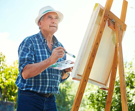 An elderly man painting his next masterpiece at Comfort Residence