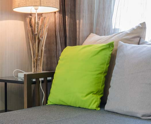 A green pillow stands out against the grey pillows at Comfort Residence