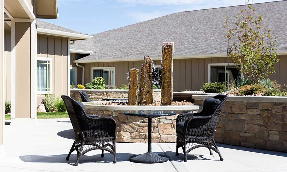 Sit outside and enjoy the fountain at Juniper Glen Alzheimer's Special Care Center