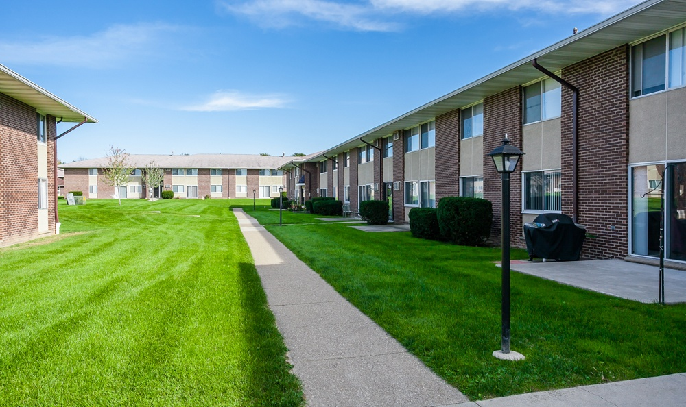 Sidewalks and lawn at Creek Hill Apartments in Webster, NY