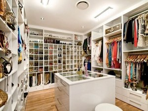 Walk in closet with tons of page and a dresser in the middle