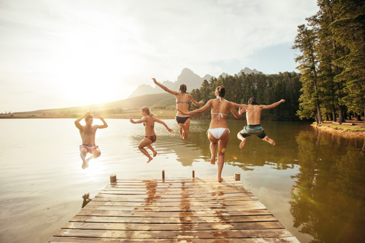 People jumping off a dock into water