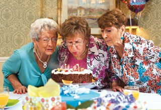 Residents blowing out candles at the senior living in Rainbow City