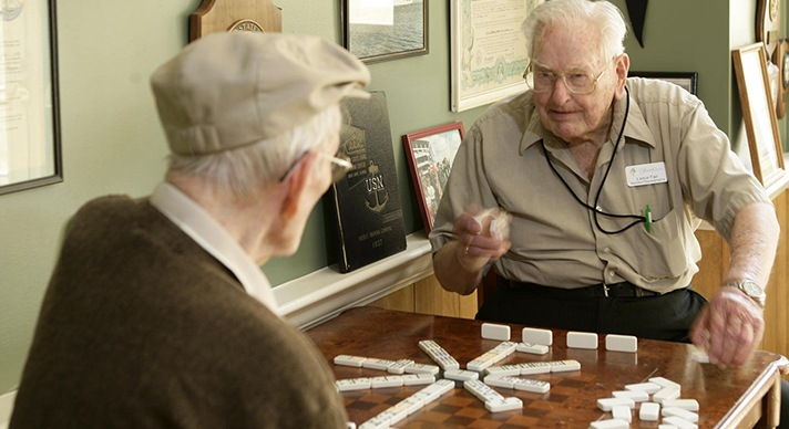 HarborChase residents play dominoes
