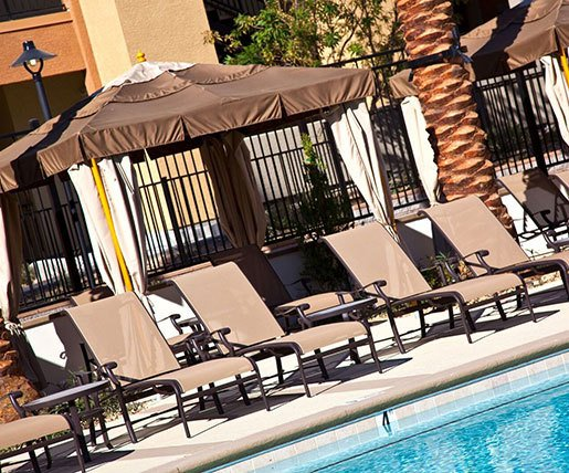 Relaxing poolside lounge chairs at Avanti Apartments