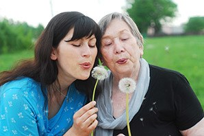 Resident and daughter blowing dandelion seeds at the senior living in Tallahassee