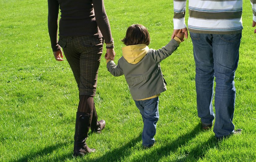 Parents and child walking at Sterling Park Apartments in Brighton, CO
