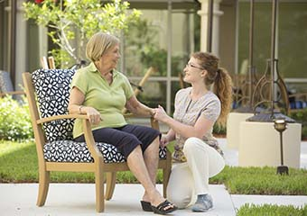 A  senior living resident chats with a caregiver.