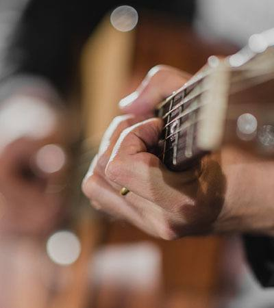 Man playing guitar in Nashville near West End Village
