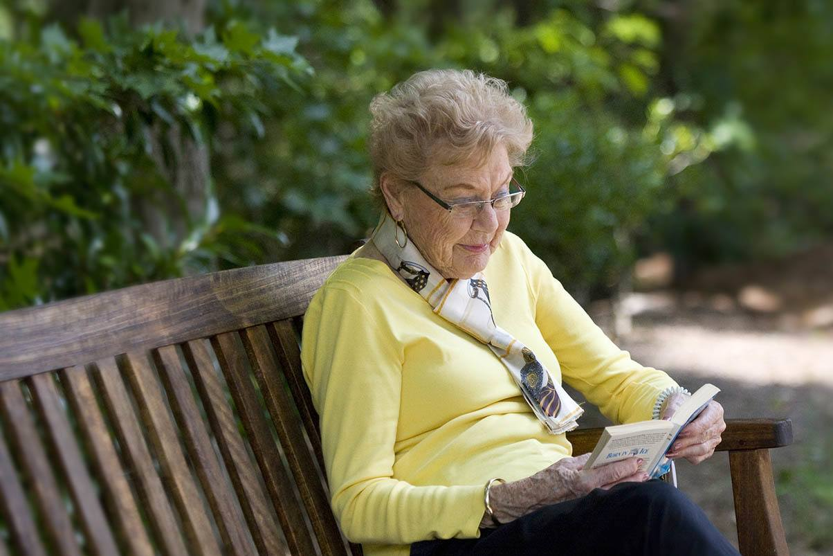 Senior woman enjoying a good book outside at Magnolia Glen