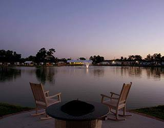 Two chairs on the pond at sunset