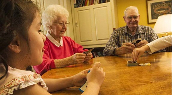 Seniors playing cards with someone's granddaughter at Regency Newcastle in Newcastle, WA