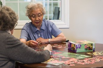Two ladies putting a puzzle together