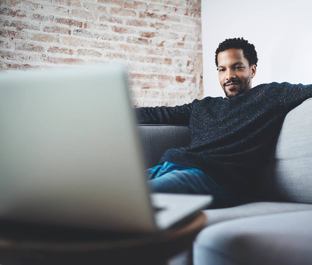 Man on couch enjoying a movie on laptop