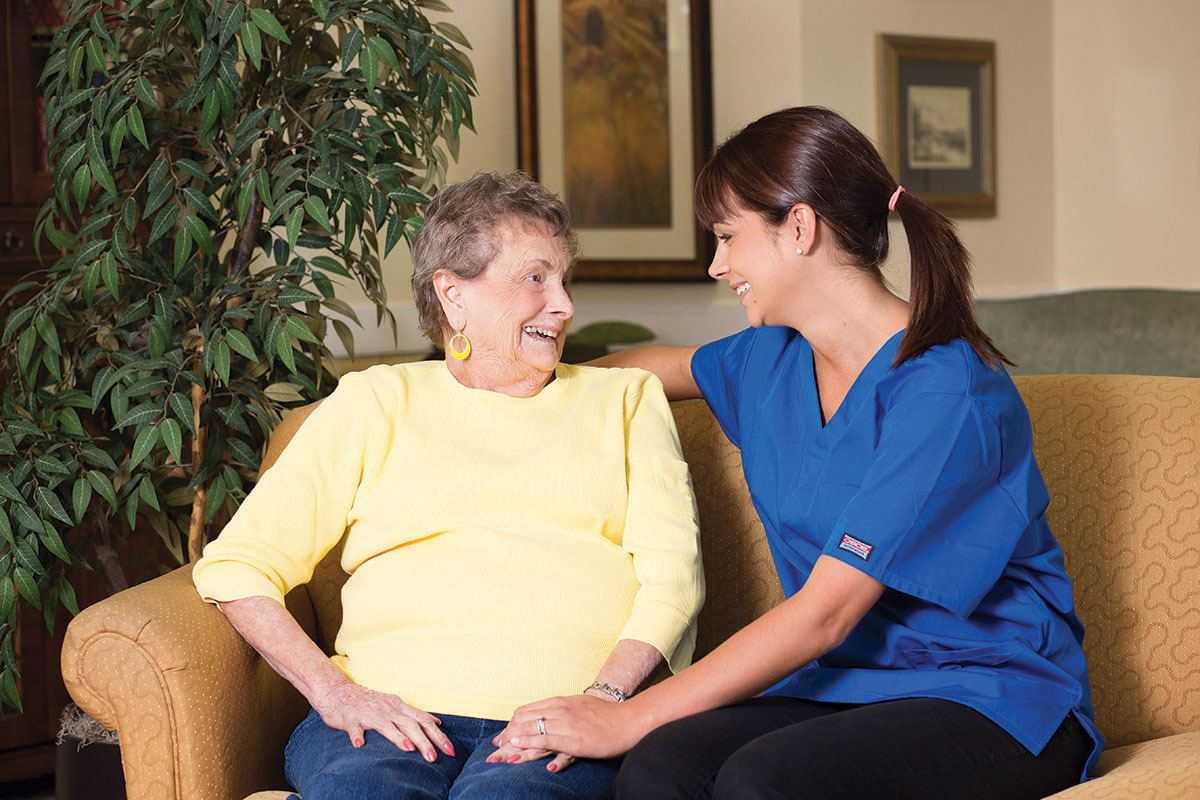 Nurse sitting with Lone Mountain Memory Care resident