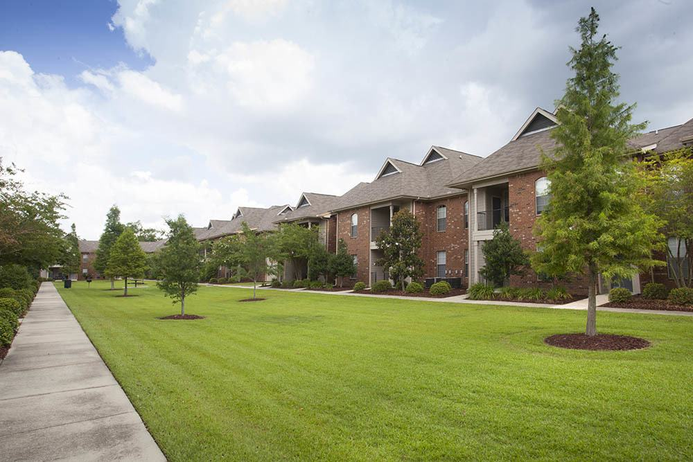 Fountain Lake Apartments Are Surrounded By Green Grounds