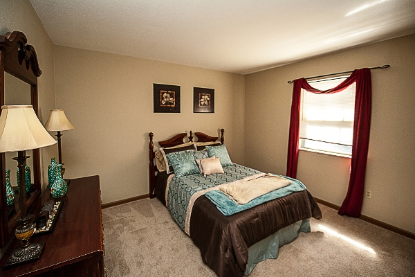 Bedroom view at Spring Hollow Apartments including hardwood flooring and stainless steel appliances