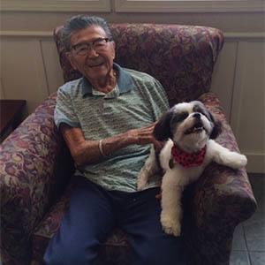 Man holding a dog at The Terraces at Park Marino in Pasadena