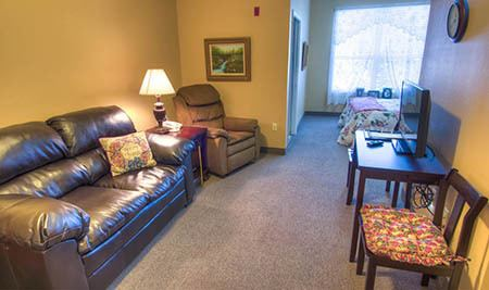 Couch in living room at Mansion at Waterford Assisted Living