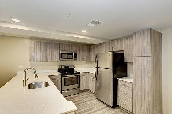 Updated kitchen with hardwood flooring at The Warwick Apartments