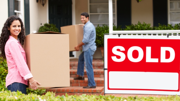 Couple moving into new home with sold wign