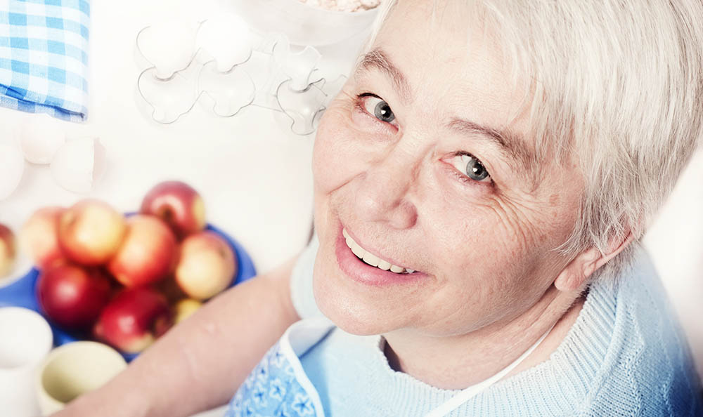 Smiling Woman With Apples at Sunnyside Meadows Memory Care in Happy Valley, OR